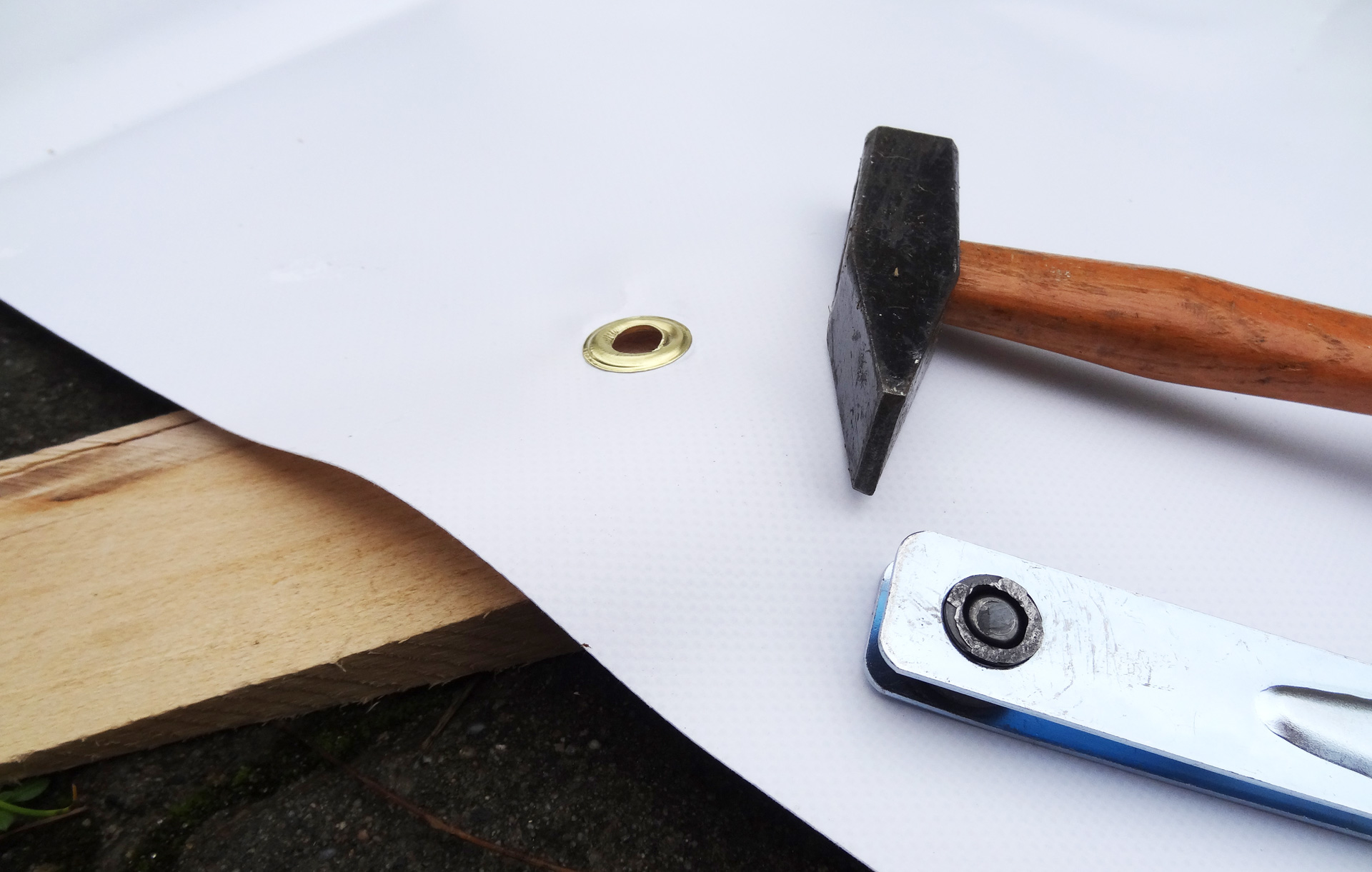 Punch the lugs into the tarp with a hammer.